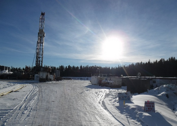 Oilfield Trucking. Arriving at a drilling rig in remote area. Notice the worker camp on the right.