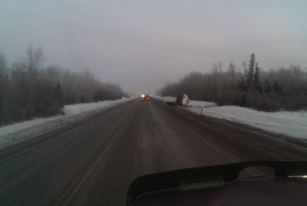 Oilfield Accidents. Bobtailing truck slides in the ditch on an icy road.