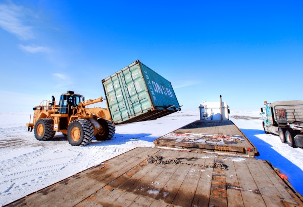 Ice Road Loads. Loader unloading containers at the mine