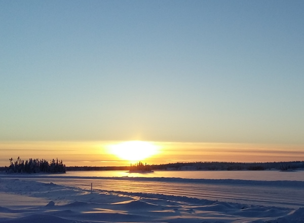 Sunrises, sunsets, sun dogs, Northern Lights and skies. Sunset over Waite Lake on the ice roads.