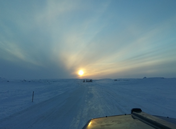 Sunrises, sunsets, sun dogs, Northern Lights and skies. A setting sun splashes some rays and colour over the ice roads.
