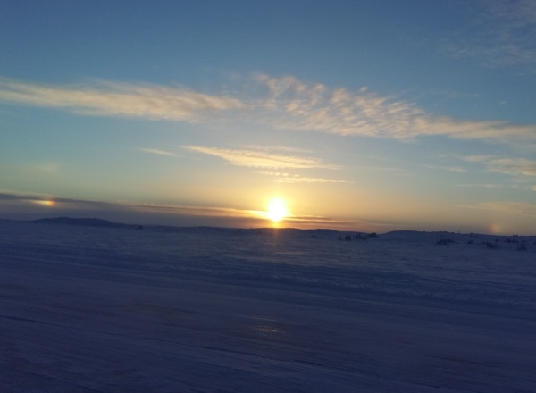 Sunrises, sunsets, sun dogs, Northern Lights and skies. The sun rises in Northern Canada on the ice roads producing a sun dog with no halo.
